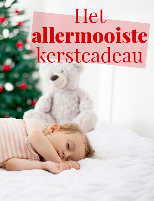 kind slaapt voor de kerstboom
