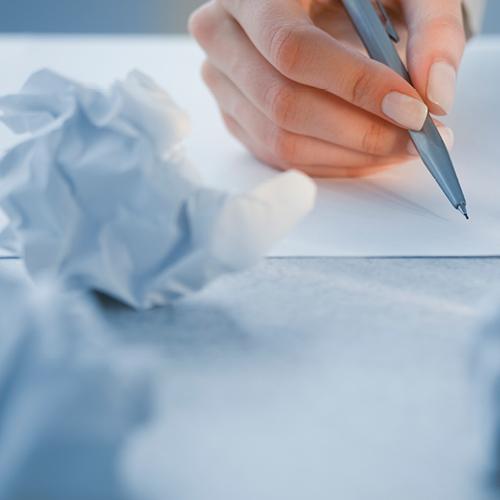 schrijvende hand met proppen papier