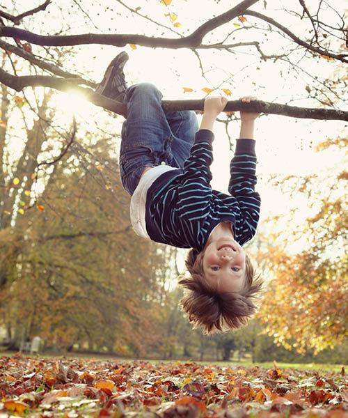 kind hangt aan boom