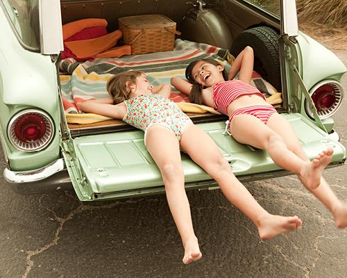 Kinderen liggen in de achterbak van groene auto