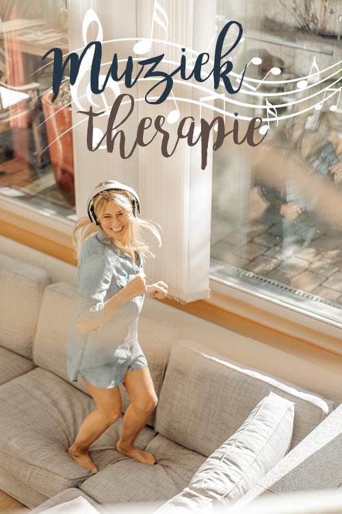 Een blije vrouw met headphones op dansend op de bank thuis