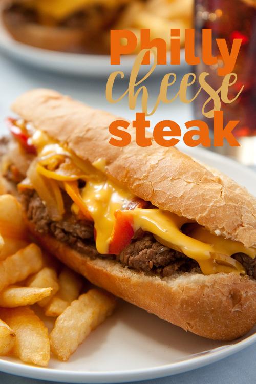 steak op broodje met kaas en friet op een bord