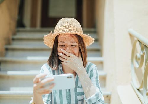 Lachende tiener met telefoon in hand