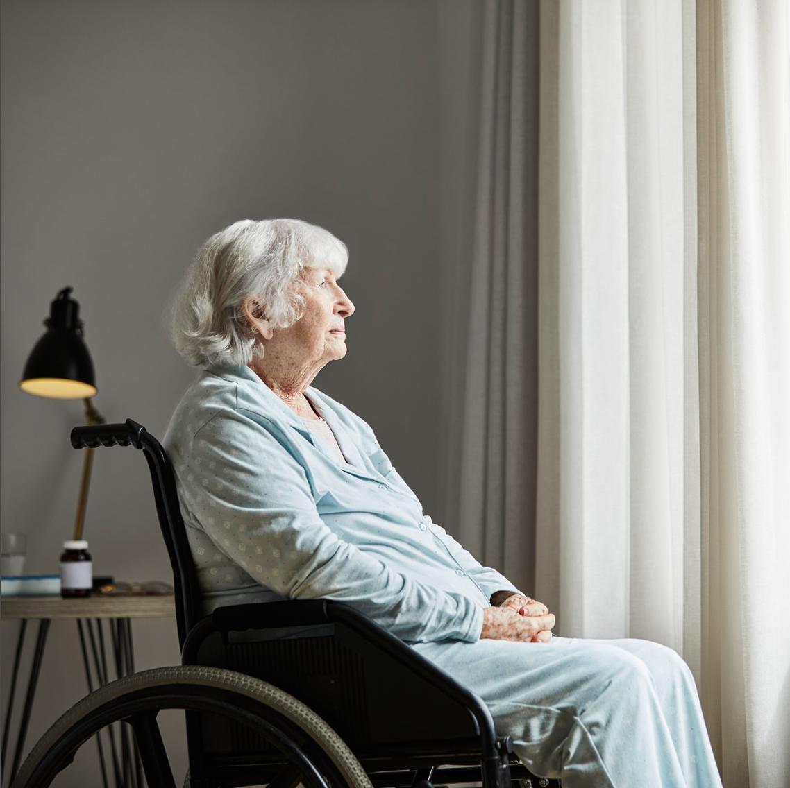 oude-vrouw-dame-eenzaam-kijkt-uit-raam-verzorgingstehuis-rolstoel