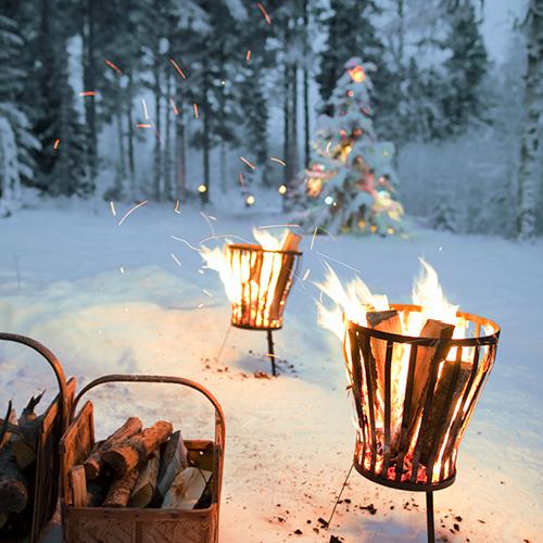 Een achtertuin vol met sneeuw en een kerstboom en vuurkorven